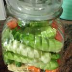 Wurzelgemüse in Scheiben, Zwiebeln in Monde schneiden, Tomaten achteln, Baby-Maiskolben vierteln. Währenddessen den Sud kochen: Alle Gewürze und in einen Topf geben und aufkochen lassen, dann das Gemüse für 3 Minuten dazugeben. Im Einweckglas Gurken schichten, einen Löffel ins Glas stellen, dann bis über die erste Schicht Gurken, den heißen Sud gießen.