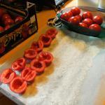 Die Tomatenhälfen mit der Schnittfläche nach oben auf Salzbett legen