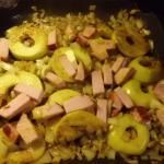 Apfelscheiben Zwiebelwürfel und Kasslerstreifen mit Curry