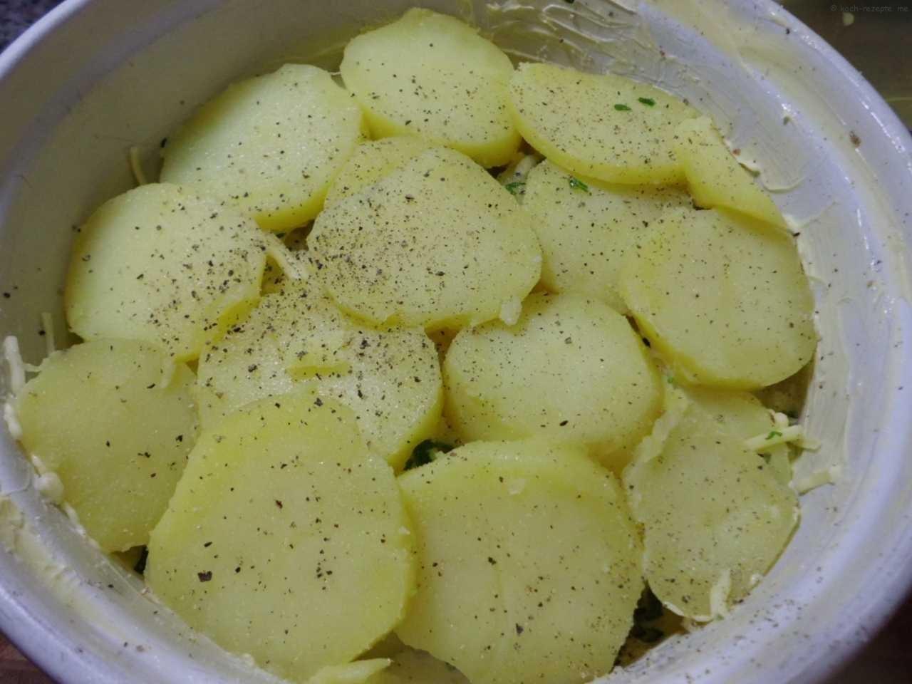 Kartoffelscheiben in gefetteter Auflaufform schichten und würzen