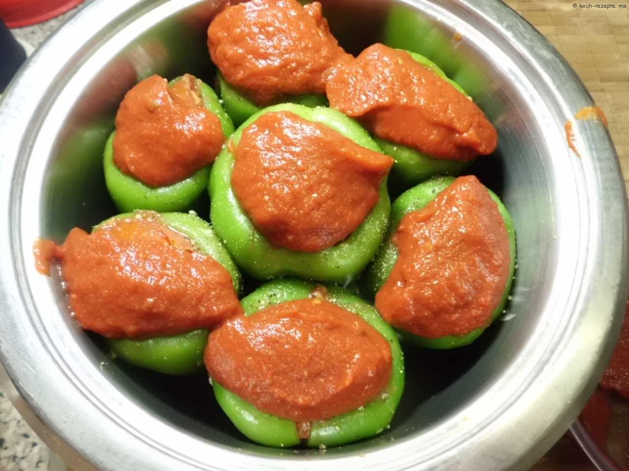 den Rest Tomatenpüree auf die Paprika geben ein Glas Wasser dazu geben
