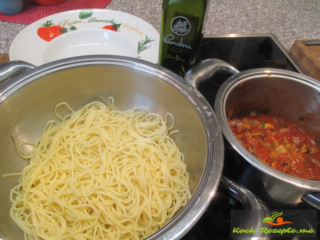 Spaghetti gekocht auf den Teller mit den Miesmuscheln in Tomatensauce anrichten