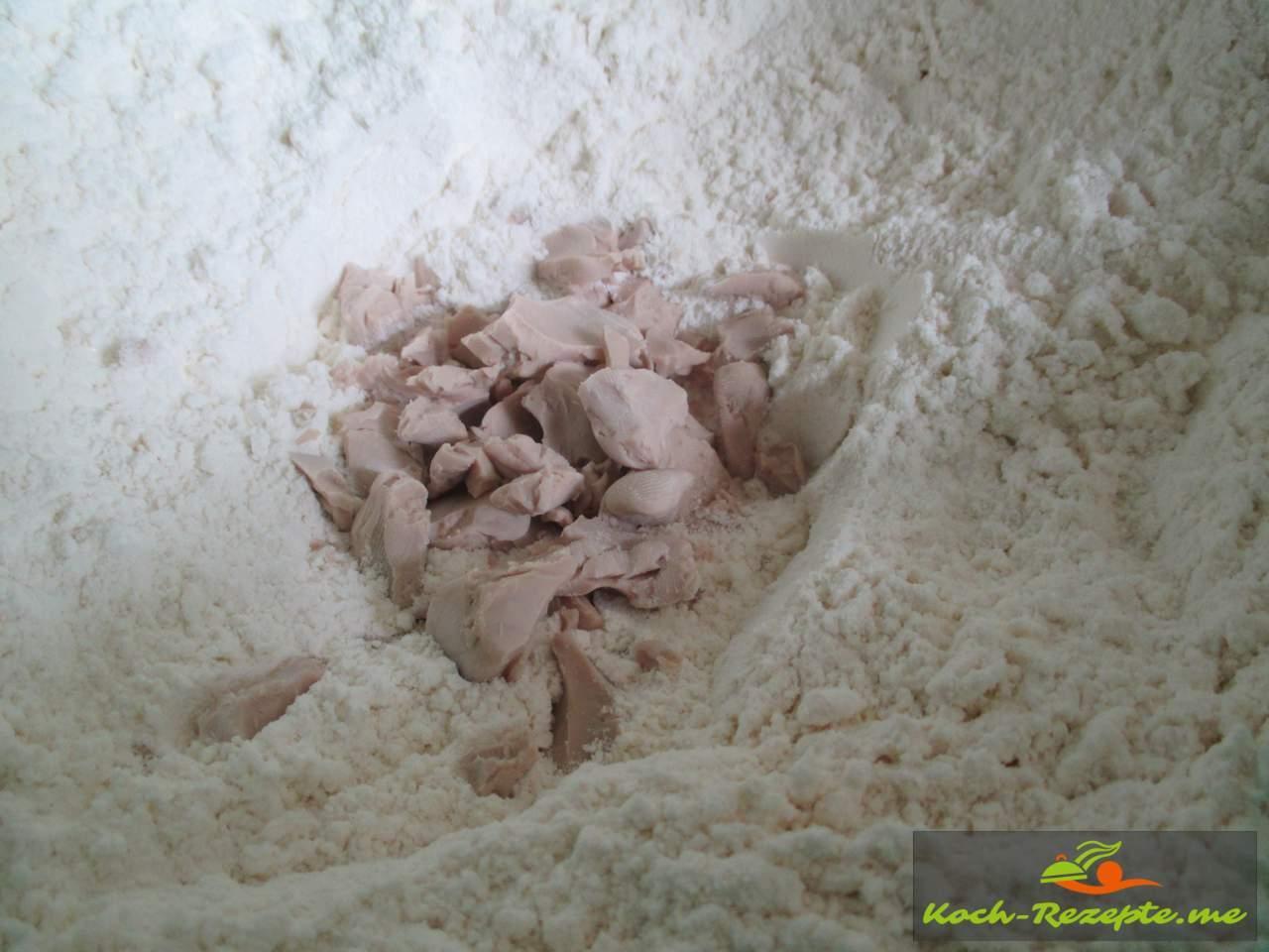 In die Mitte ein Kuhle machen und die Hefe rein bröckeln und mit Zucker undWasser einen Vorteig herstellen