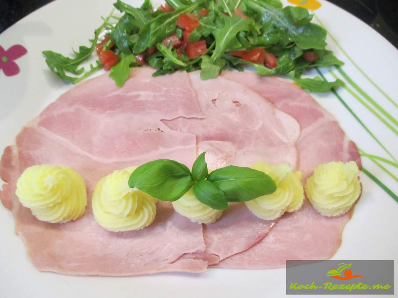 Einen Vorspeiseteller anrichten mit Vorderschinken, Salat und Kartoffelpüree