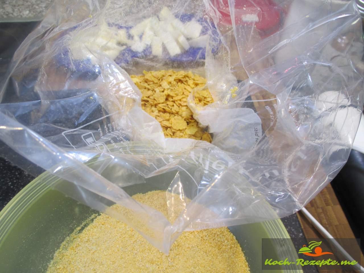 Die Kornflakes zerkleinern in einem Beutel und unter das Paniermehl mischen