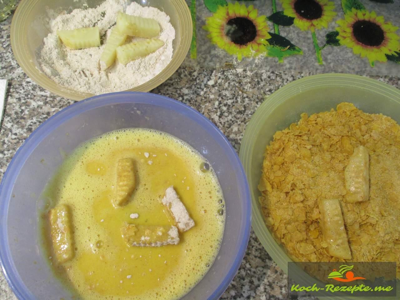 Die Stifte erst bemehlen, dann durchs Ei ziehen und dann in Kornflakes wälzen
