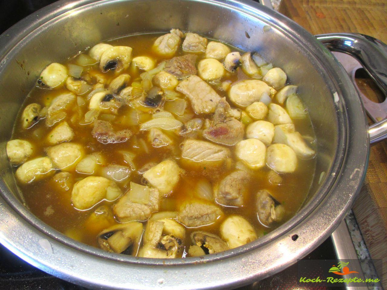 Schweinegulasch mit Zwiebeln und Champignons in Brühe kochen