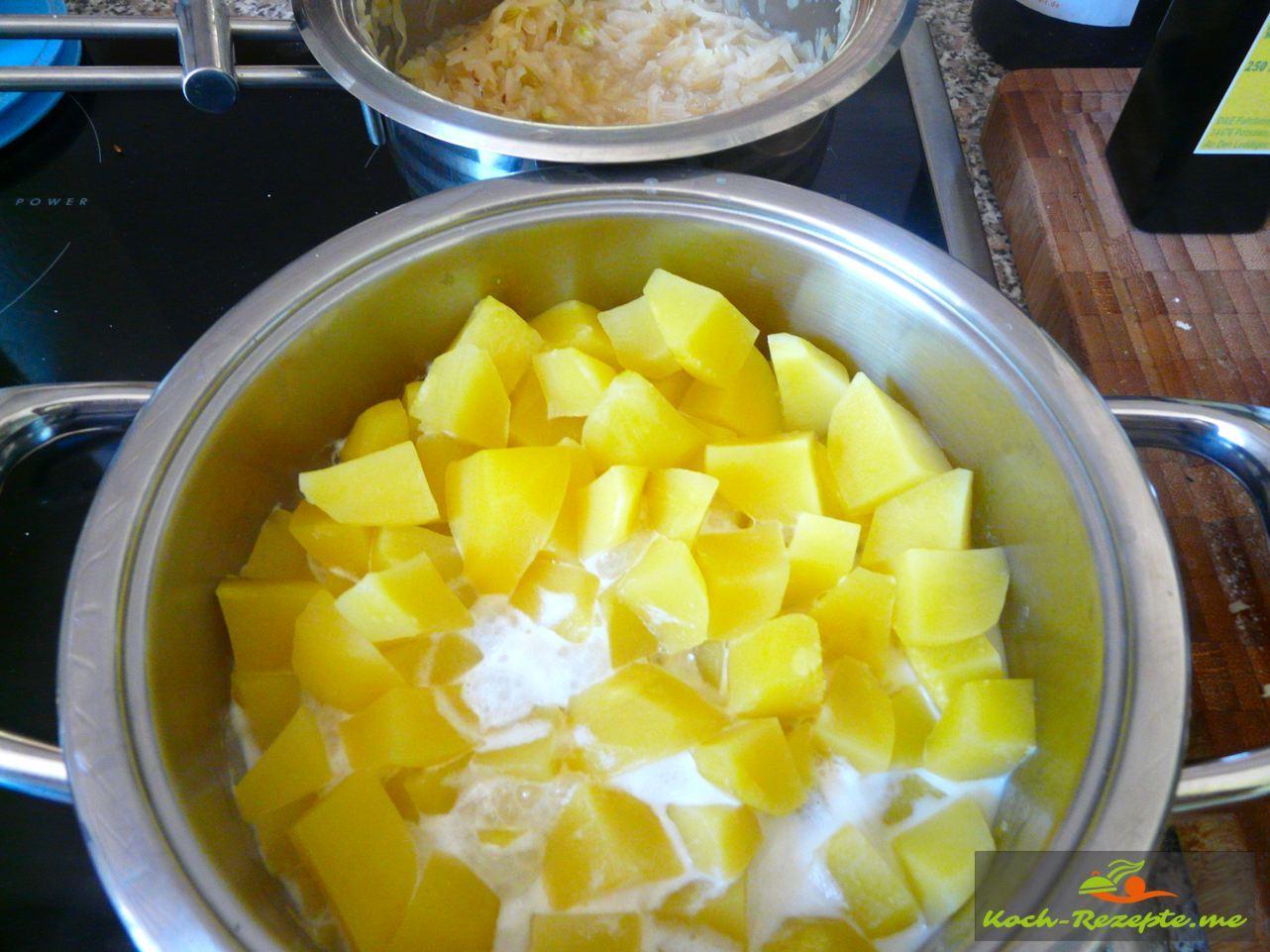 Wasser abgießen und an die fertig gekochten Kartoffelwürfel Milch geben