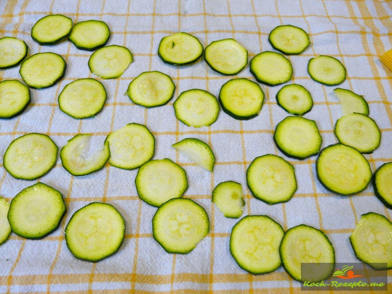 Die Zucchinischeiben in einem Tuch trocknen