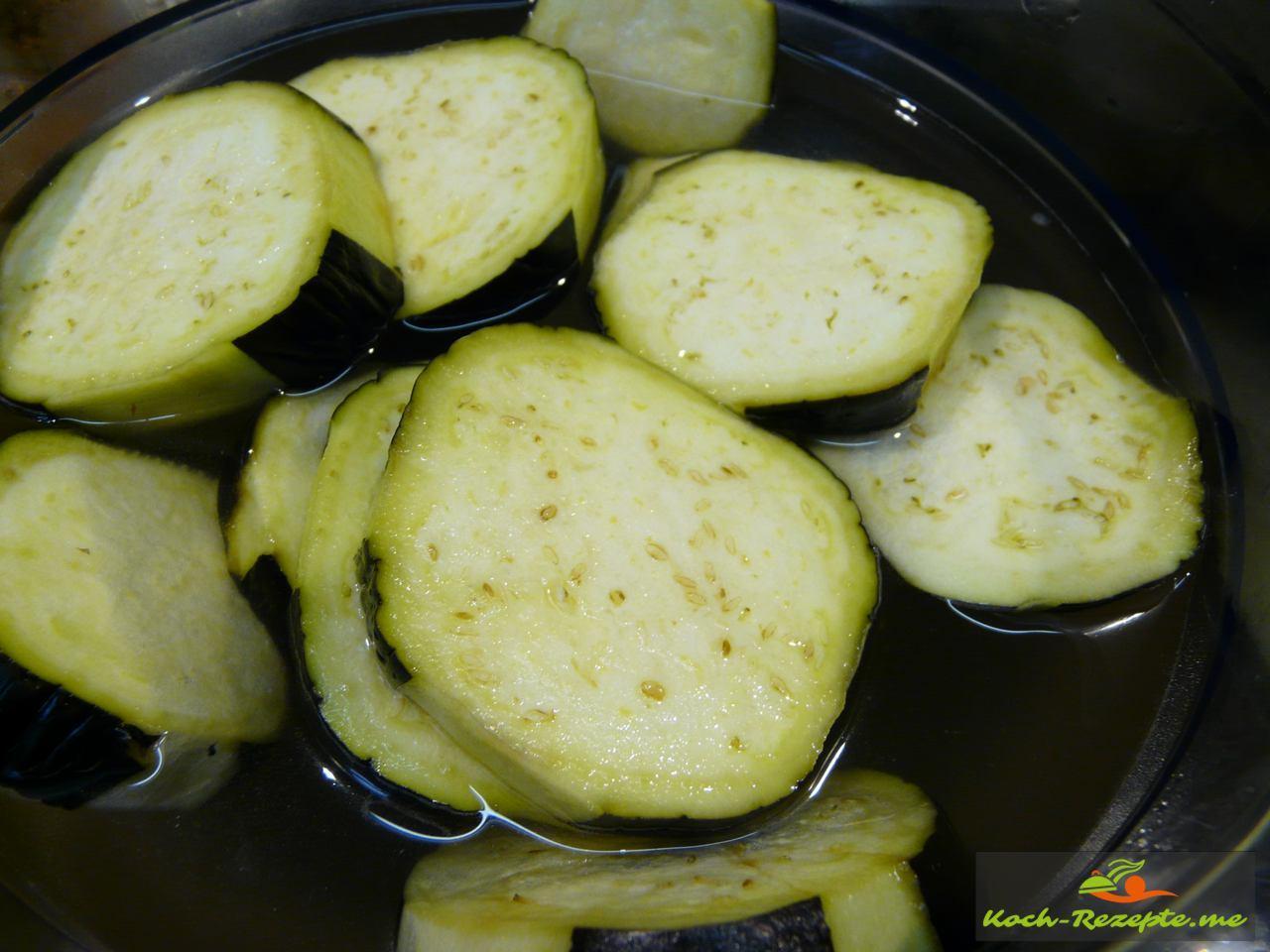 Auberginen werden 10 Minuten in kaltes Salzwasser eingelegt, dann ausgedrückt und geviertelt