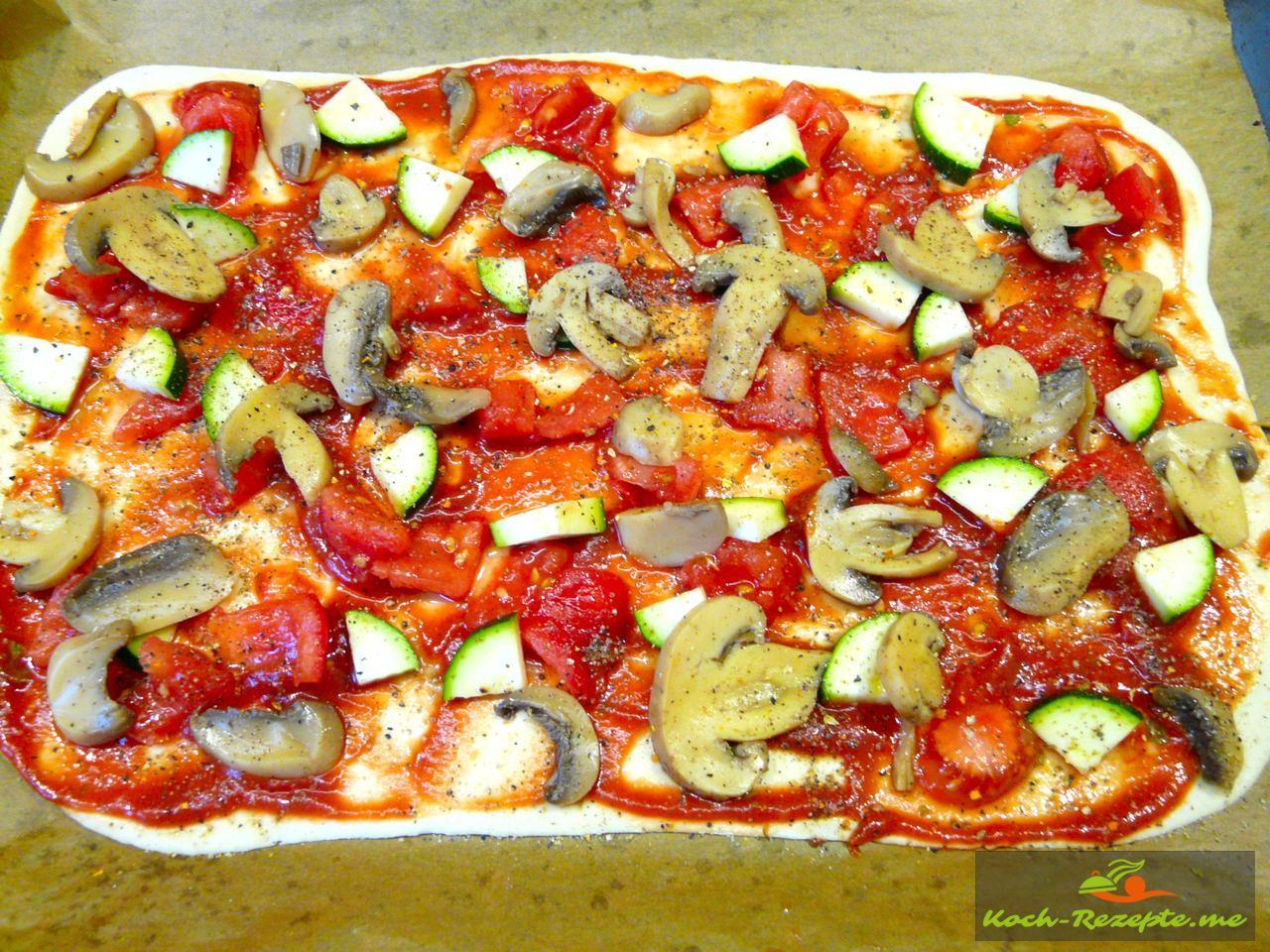 Teig ausrollen und Pizza belegen
