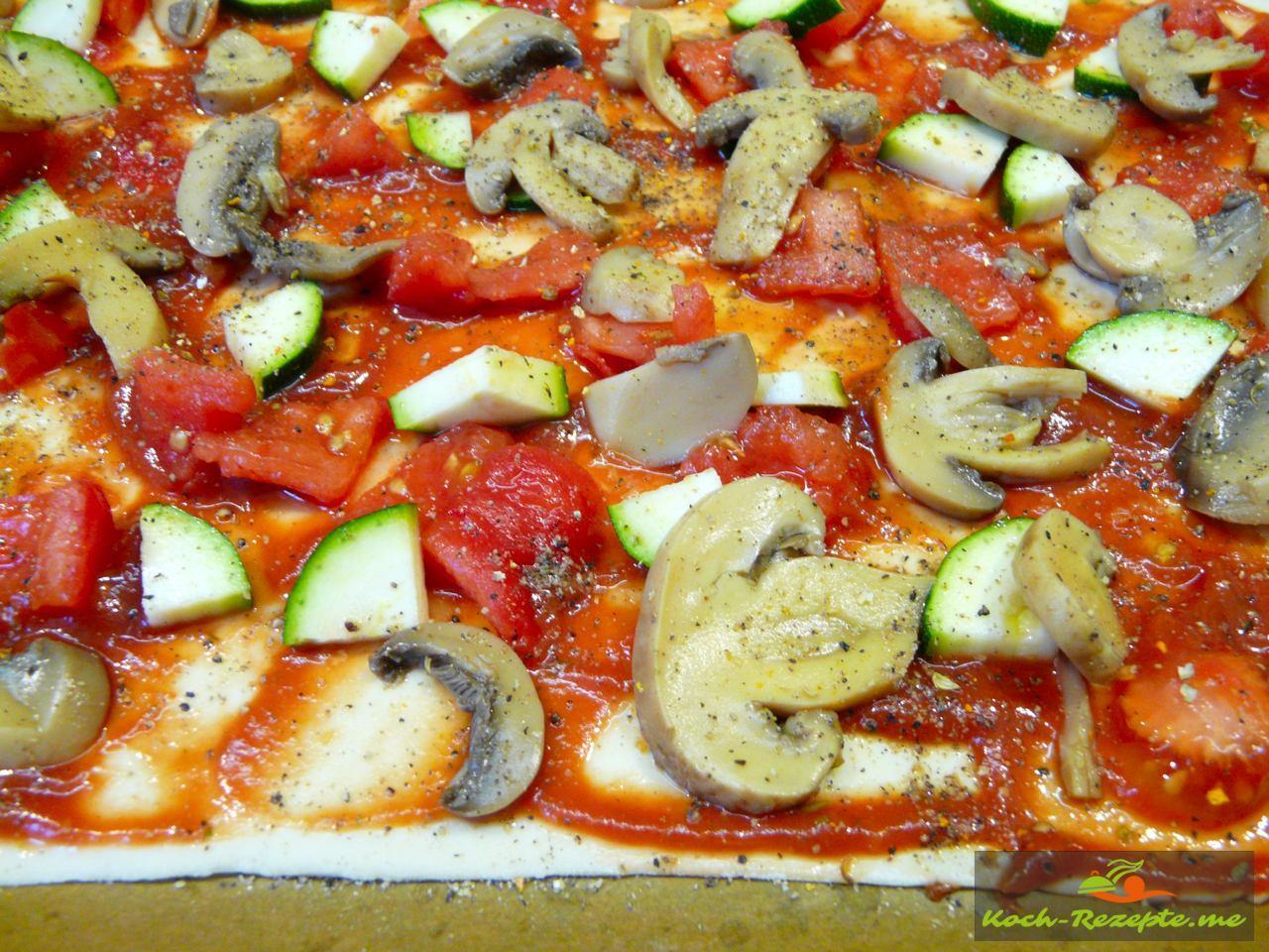 Champignonscheiben, Zucchinistücke auf die Pizza geben