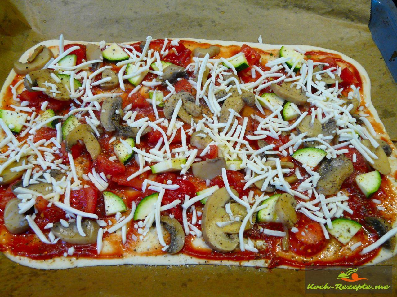 Sommer-Pizza mit Käse bestreuen