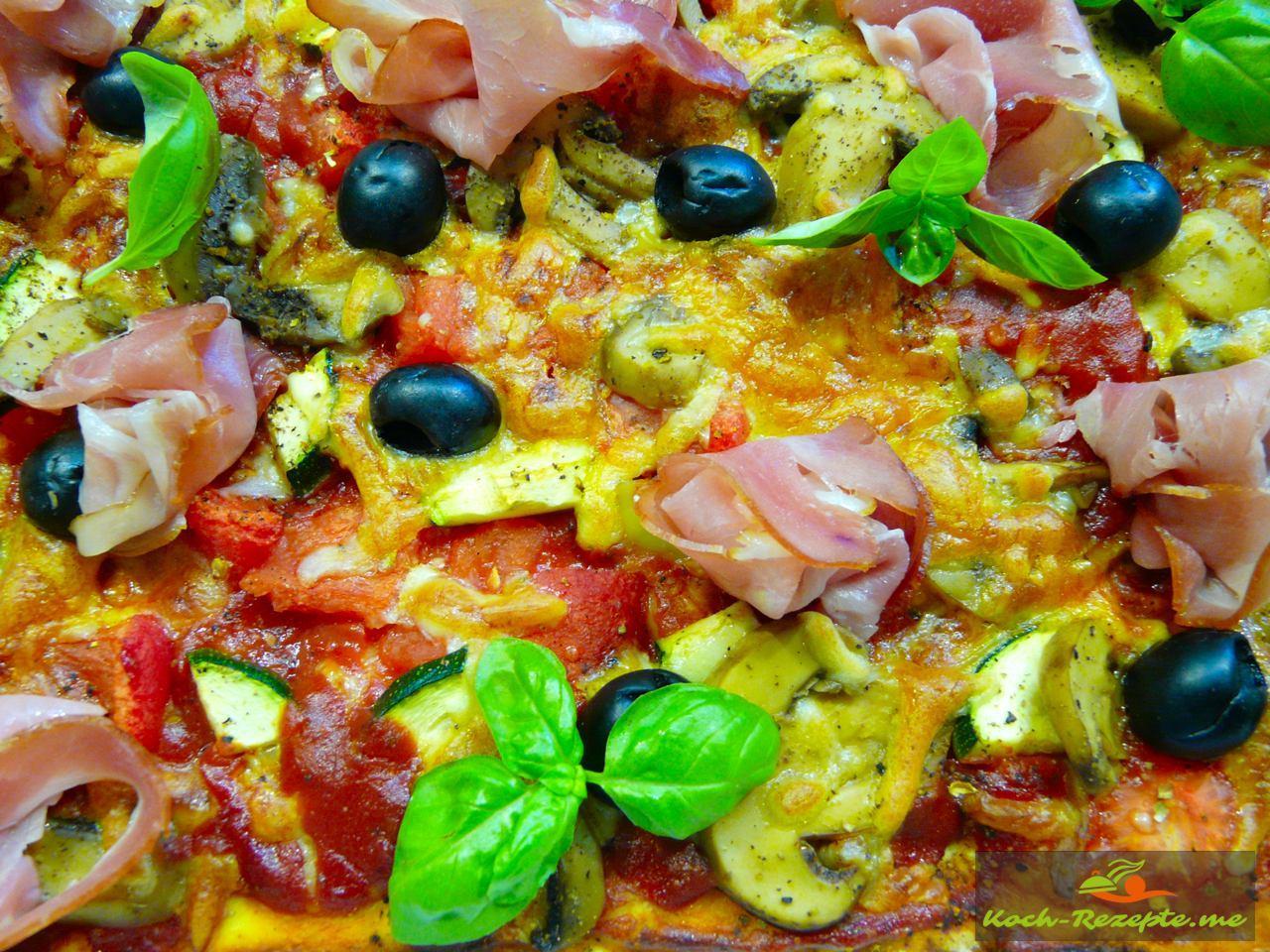 Sommer-Pizza mit Oliven, Schinken und Basilikum garnieren