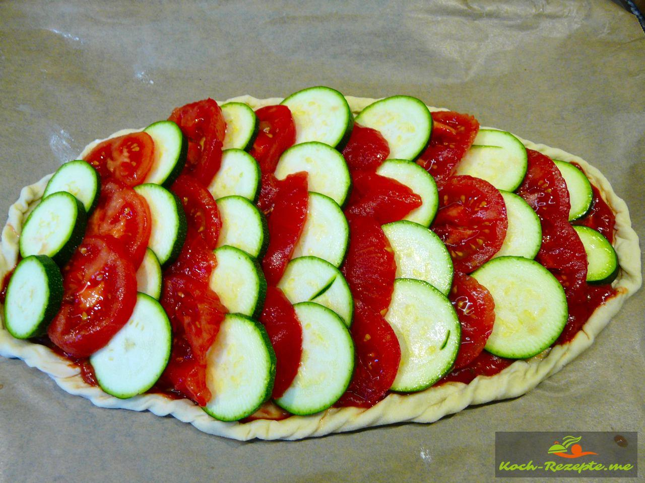 Sommer Pizza leichte Zutaten mit Zucchini und Tomaten belegen