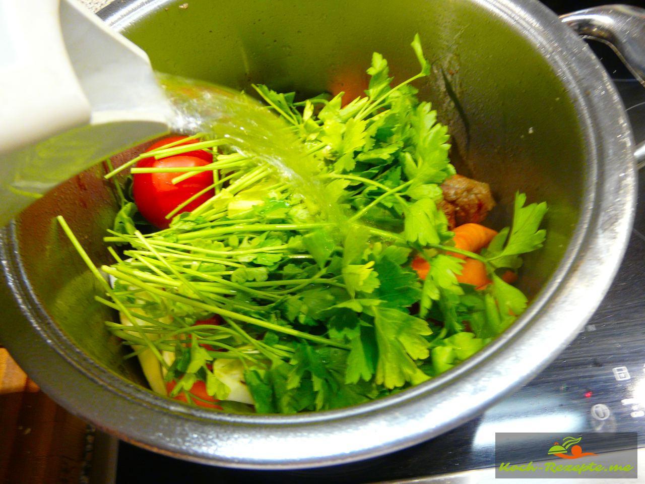 Viel Gemüse aufs Fleisch legen und alles mit Wasser aufgießen