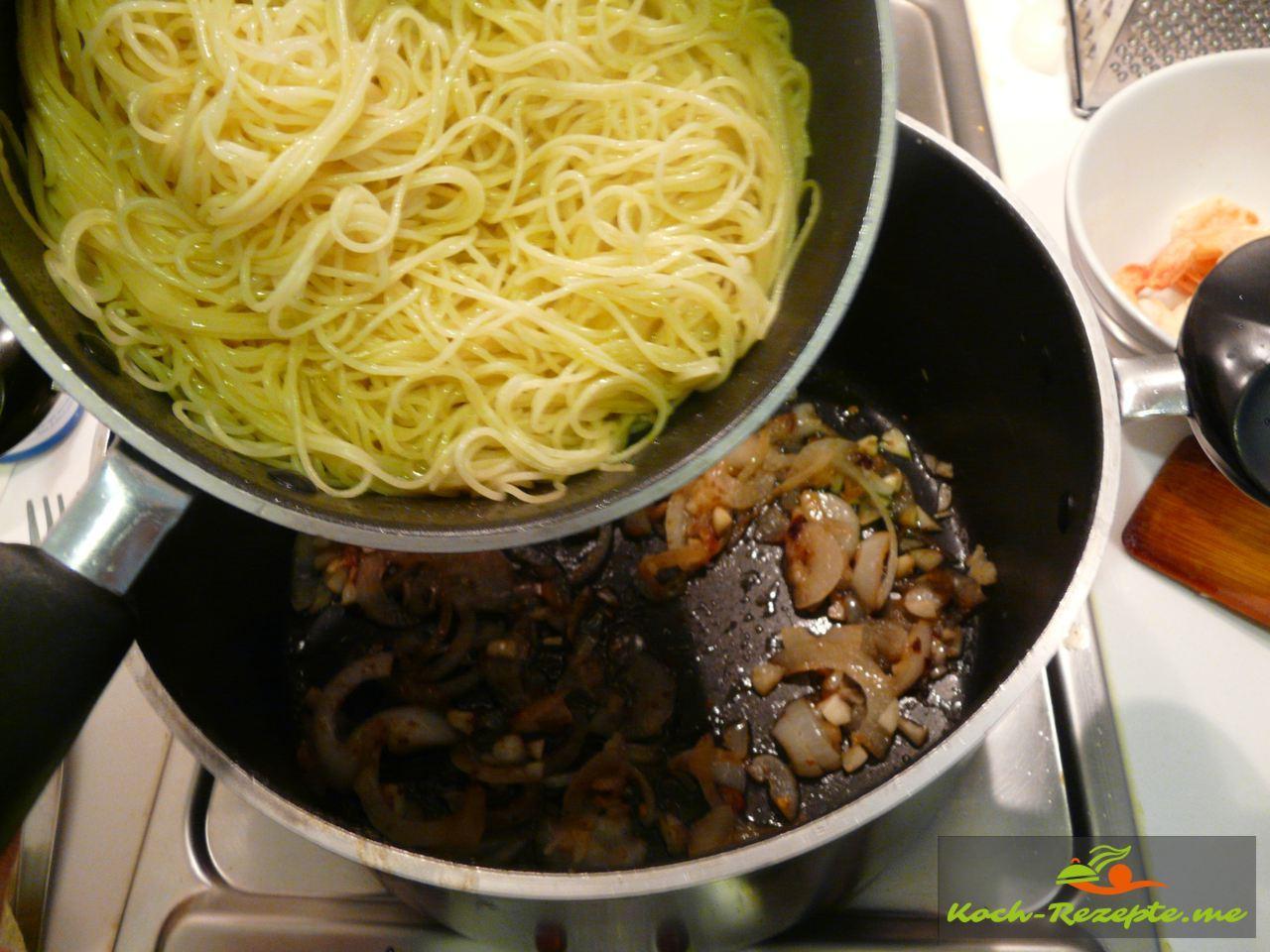 Nudeln mit Zwiebeln und Knoblauch vermischen