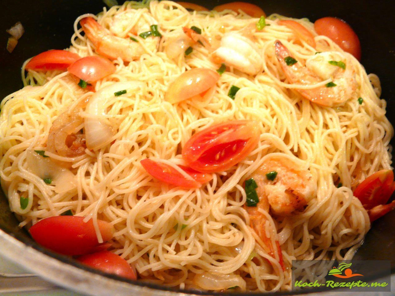 Fertige Spaghetti mit Frühlingszwiebelgrün und Tomaten vermischen