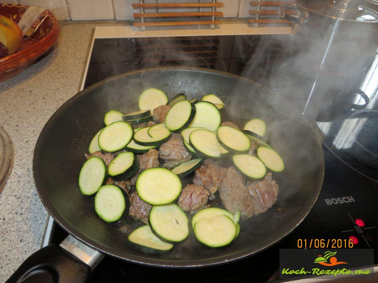 In einer Pfanne Olivenöl erhitzen, Rinderhüftsteak in Würfel kräftig von allen Seiten anbraten und mit Brühe ablöschen dann Zucchinscheiben mit schwenken