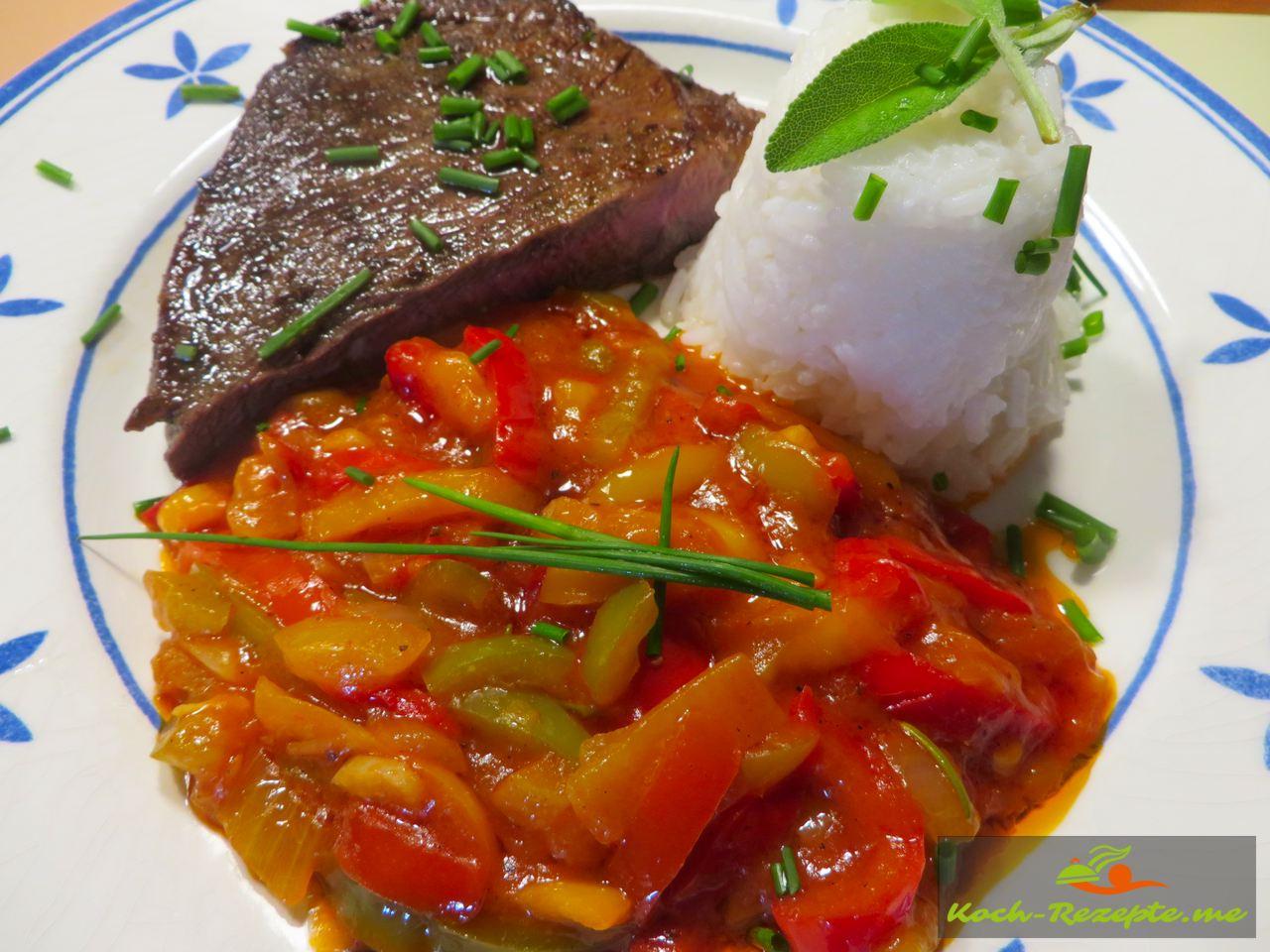 Angerichtet auf einen Teller Steak, Reis und  Piperade á la basquaise , Paprikagemüse