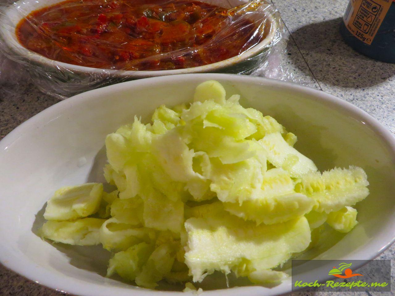 gefüllte Zucchini überbacken auf Paprikagemüse, Rezept mit französischer Bratwurst. Ausgelöffelte Fruchtfleisch der Zucchini