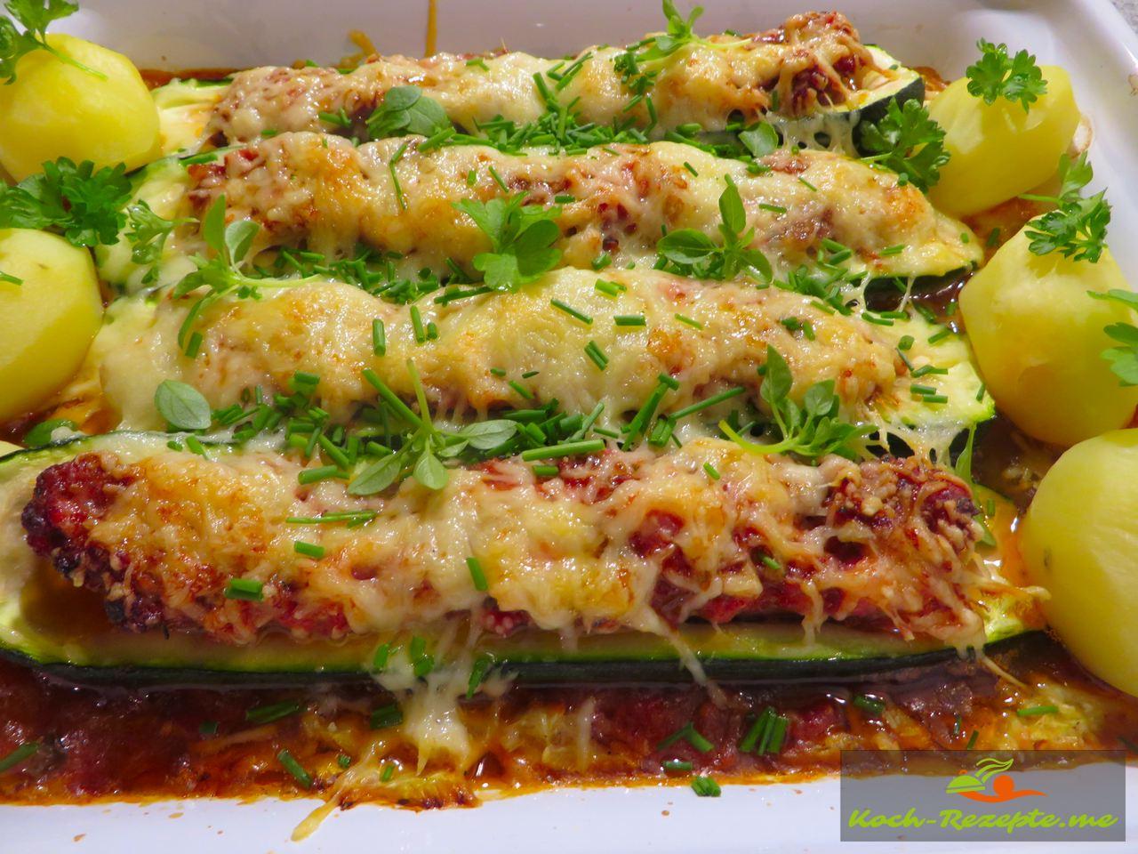 Nach der Backzeit zum Garnieren und servieren fertig gefüllte Zucchini überbacken auf Paprikagemüse, Rezept mit französischer Bratwurst.