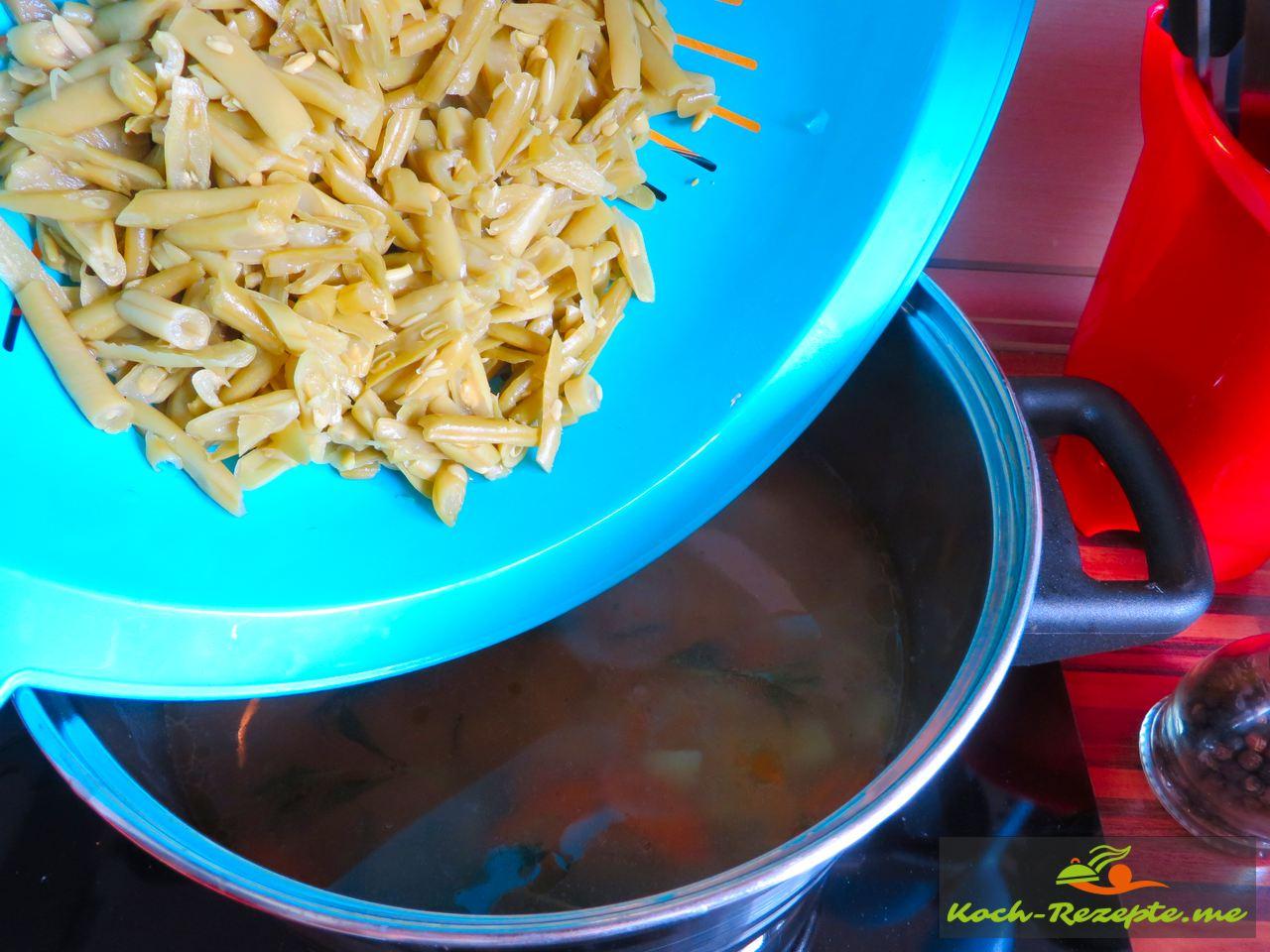die Bohnen dazu geben in die Grüne Bohnen-Buttermilch Suppe mit Katenrauch Bauchspeck.