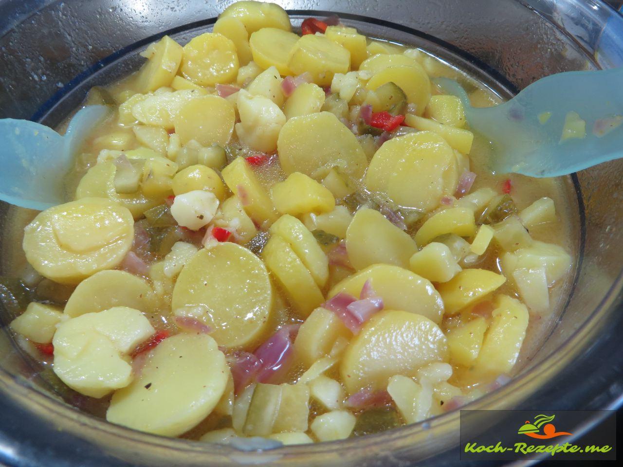 Kartoffelsalat mit Brühe und Zutaten umrühren