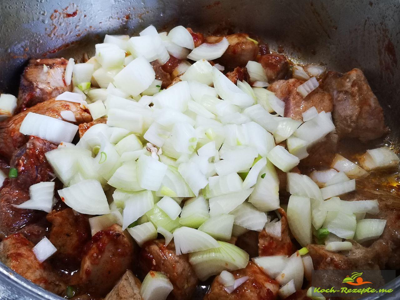 Zum angebratenem Fleisch Zwiebelwürfel gebn und anbraten