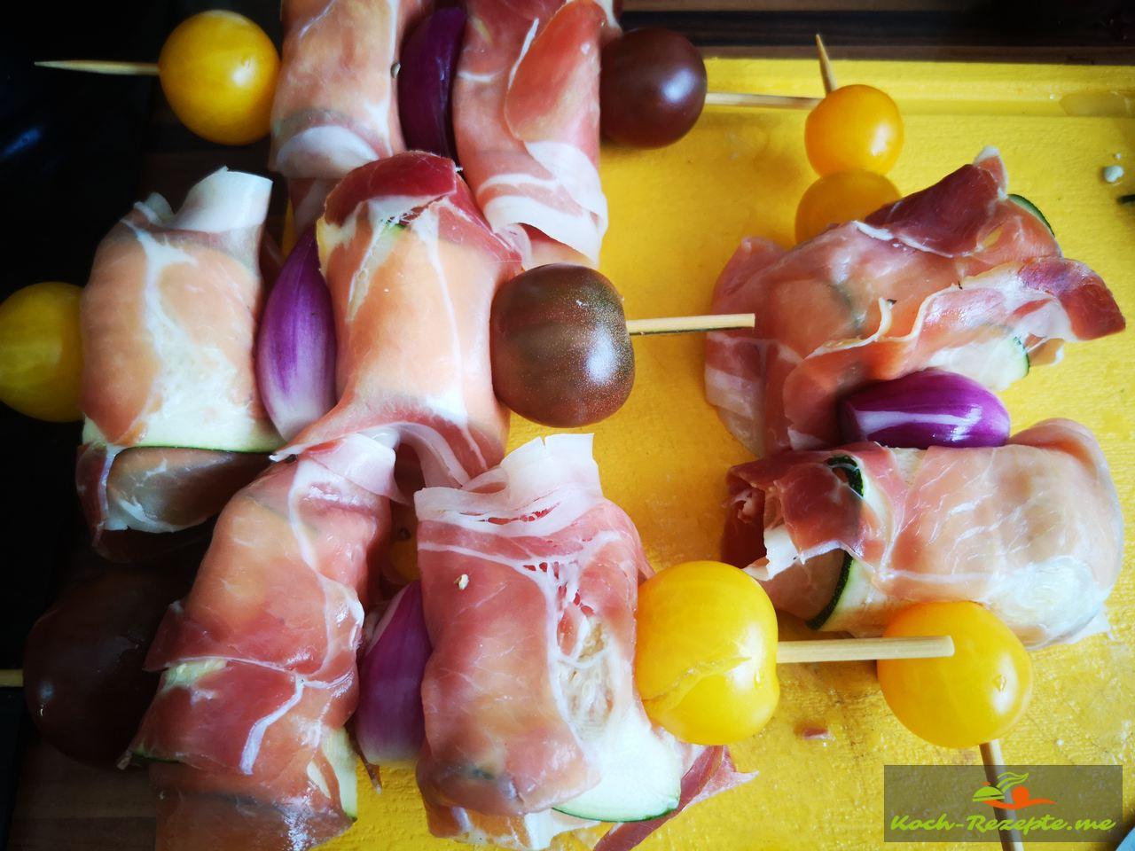auf gewässerte Spieße die fertigen Schinken-Zucchini-Käse Päckchen geben