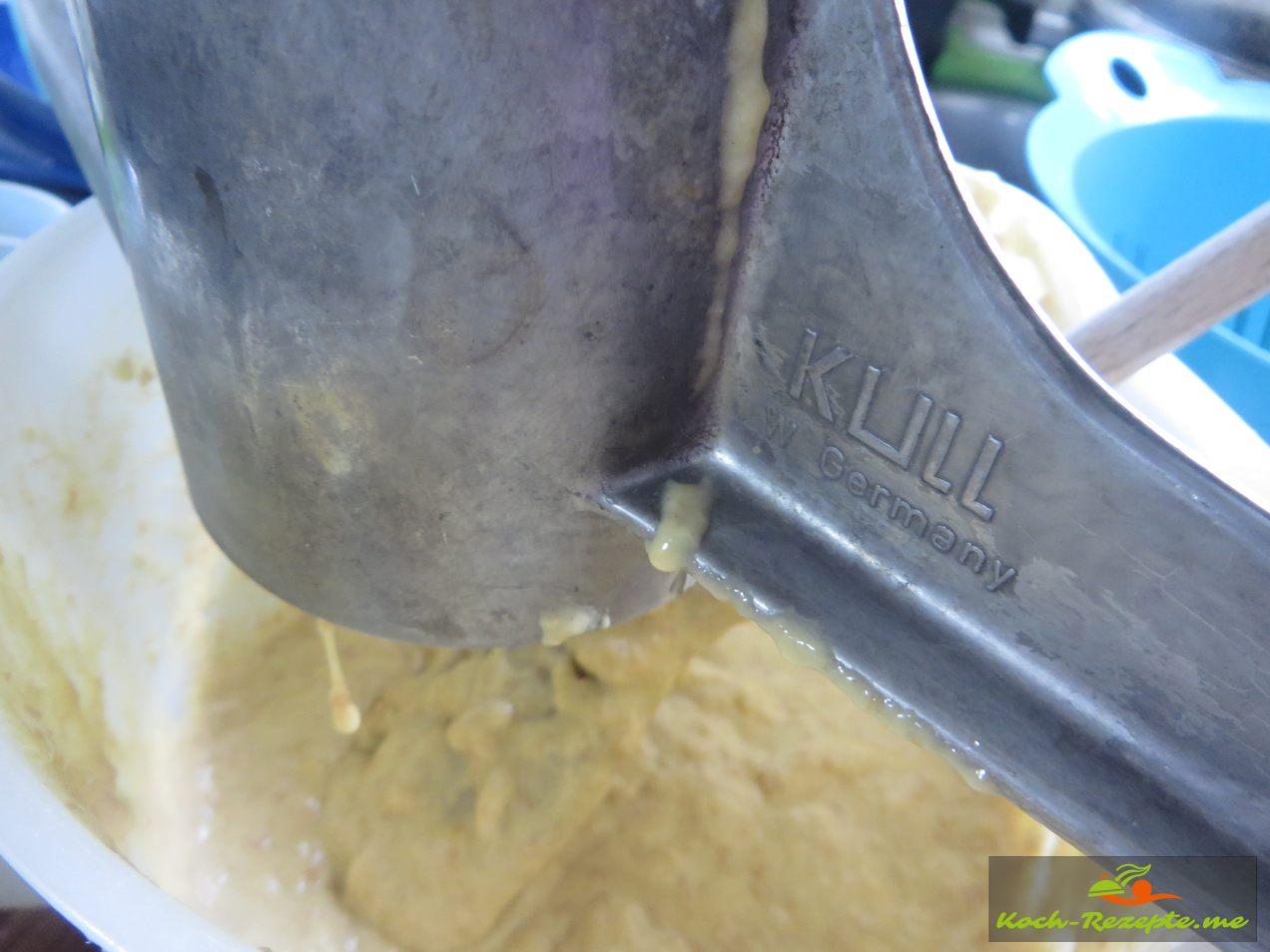 Spätzle aus der Presse ins kochende Wasser geben