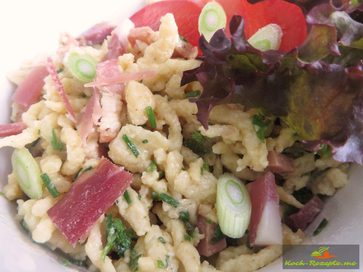 Spätzlesalat auf die Tomatenscheiben anrichten