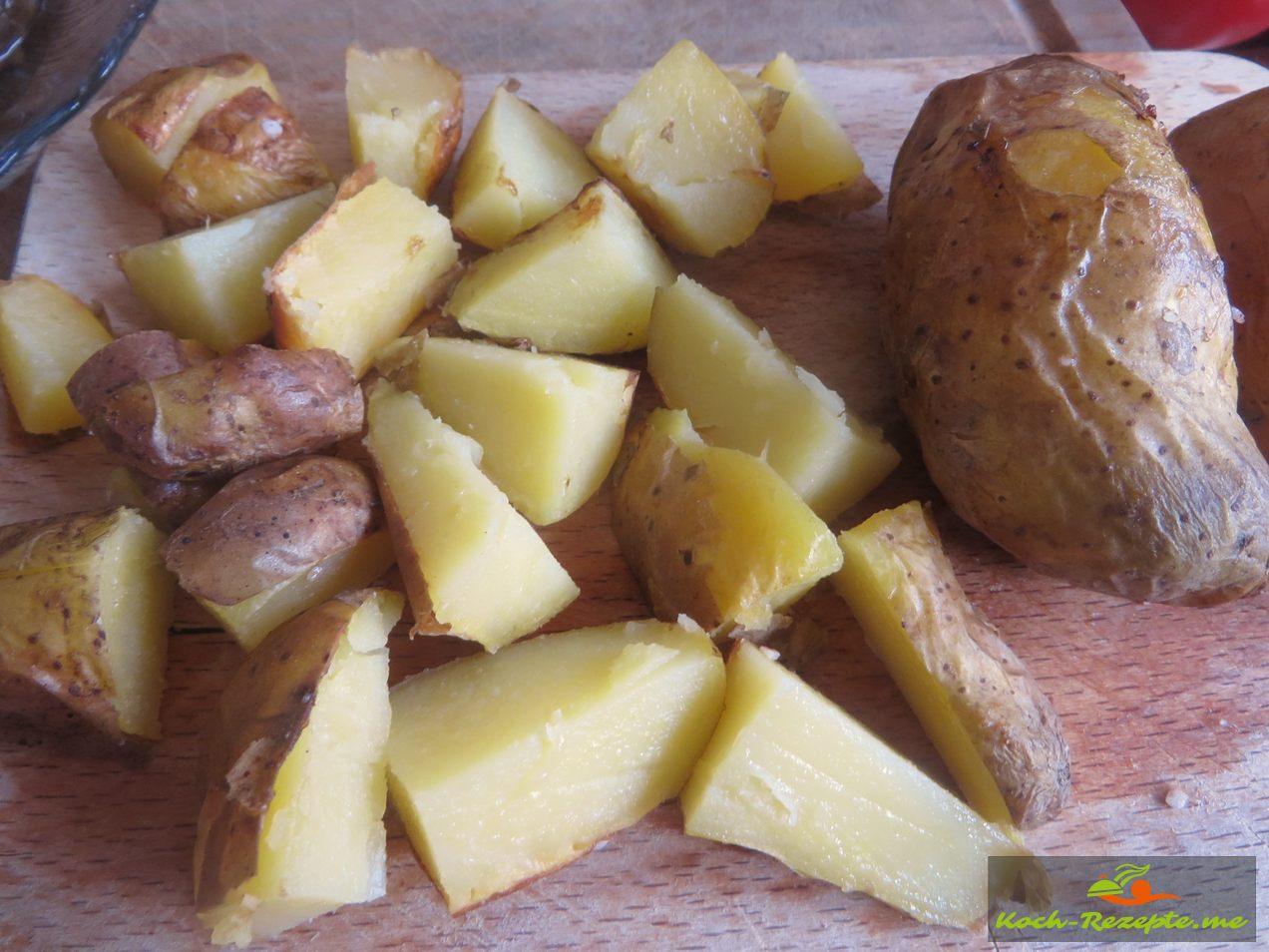 Die fertigen Ofenkartoffeln mit Haut in Stücke schneiden
