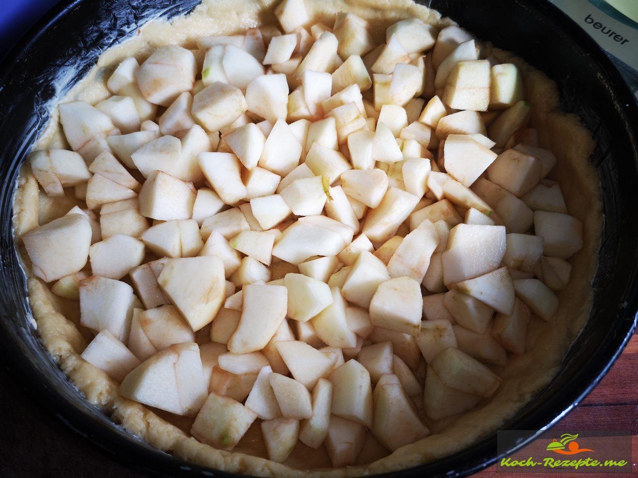 Die Apfelwürfel auf den Mürbeteig verteilen