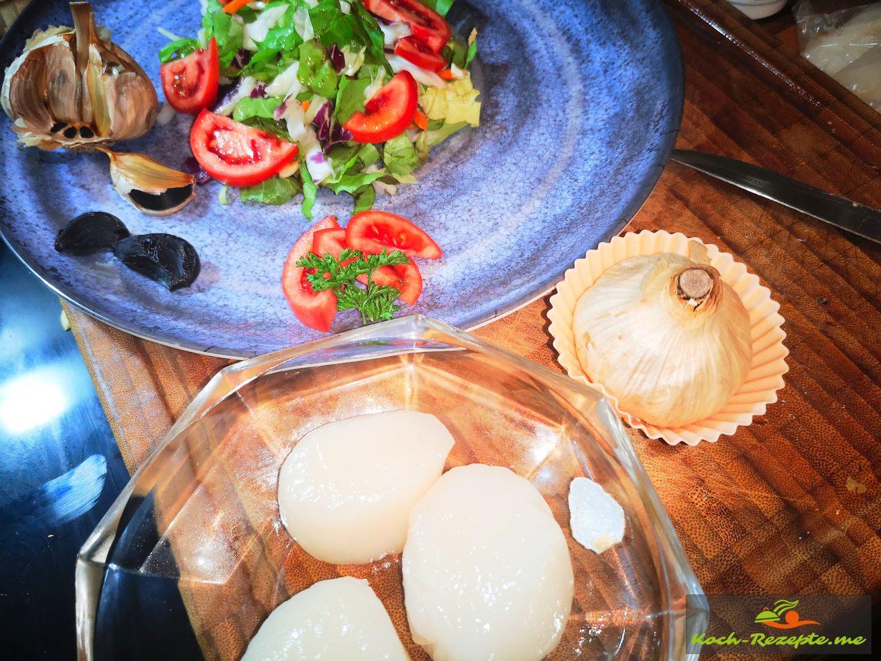 gemischter Salat mit gebratenen Jakobsmuscheln und Schwarzem Knoblauch.