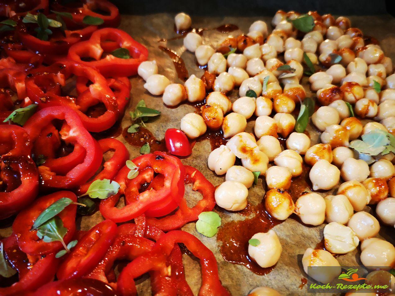 Spitzpaprika, Kichererbsen und Kirschtomaten auf ein Backblech geben