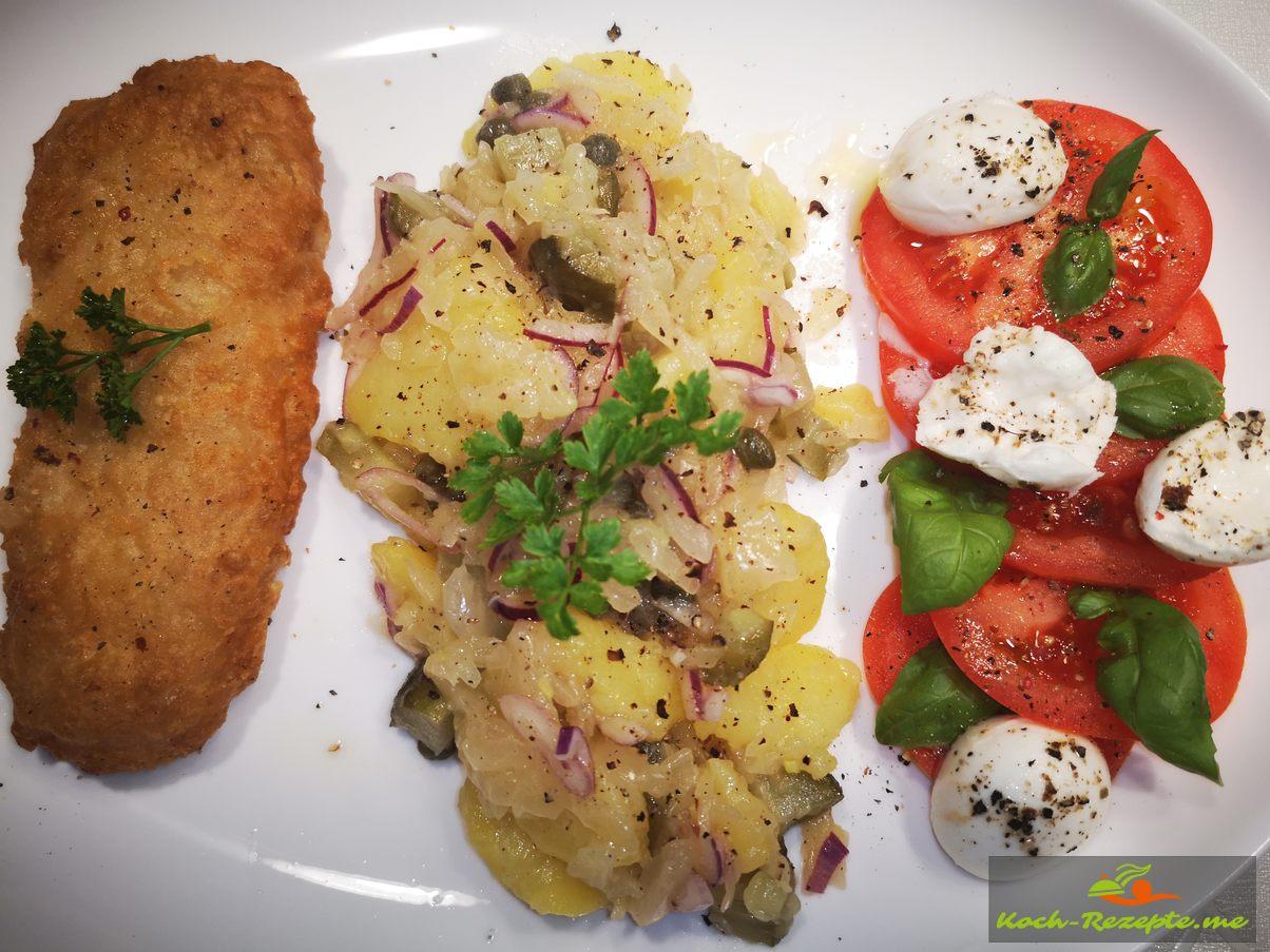 Lauwarm den Kartoffel-Sauerkraut Salat servieren, Beilage Backfisch und Tomaten-Büffelmozzarella
