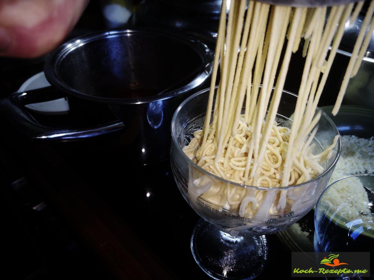 Durch die Kartoffelpresse das Vanilleeis zu Spaghettieis pressen